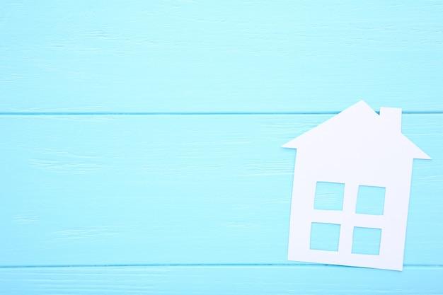 Maison en papier blanc sur fond bleu