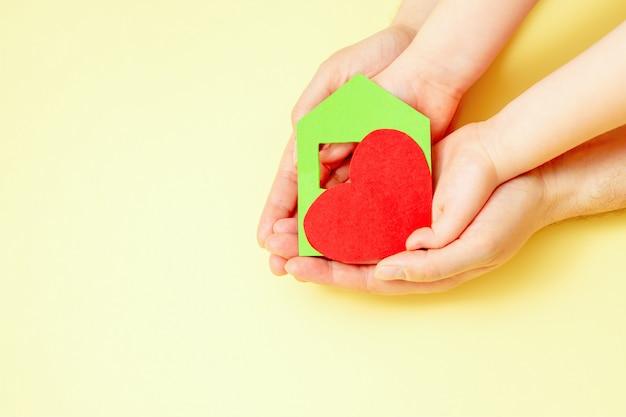 Maison de papier avec coeur dans les mains