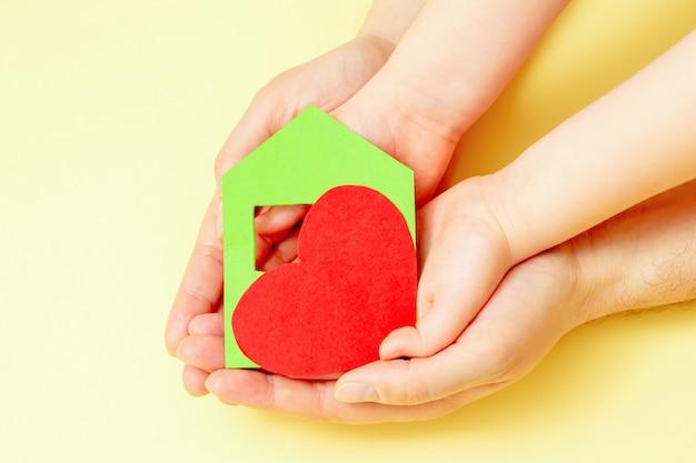Maison de papier avec coeur en mains