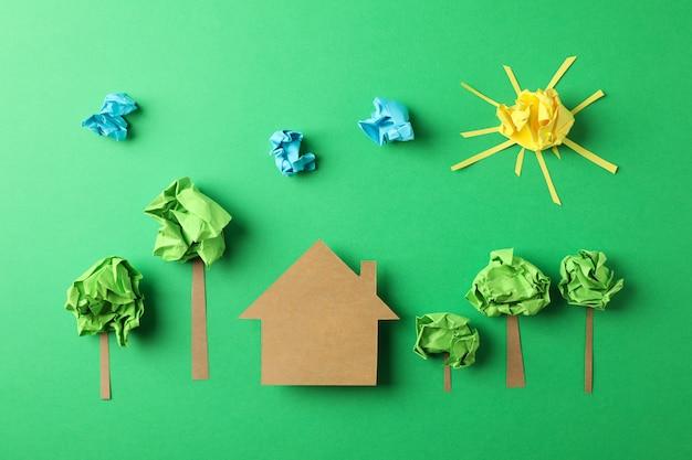 Maison en papier, nuages, soleil et arbres sur fond vert, vue de dessus