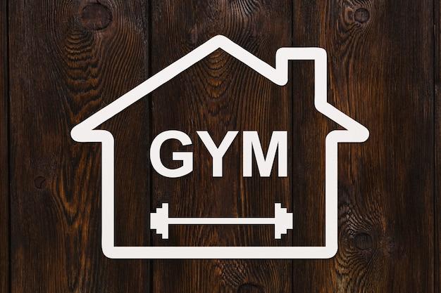 Maison de papier avec texte gym à l'intérieur sur fond de bois. image conceptuelle de sport abstrait