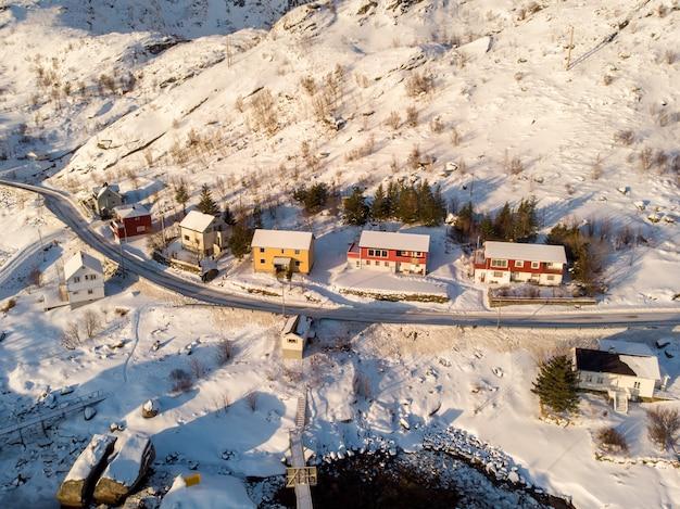 Maison de pêche colorée sur le littoral dans les chutes de neige en hiver