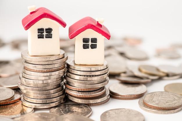 Maison sur pile de pièces, concept de financement de prêt hypothécaire.