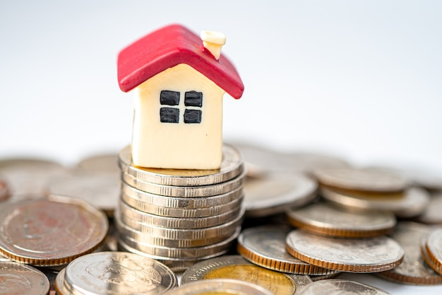 Maison sur pile de pièces, concept de financement de prêt immobilier hypothécaire.