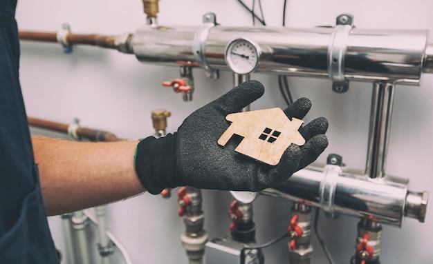 Maison plate en bois dans la main du plombier dans des gants de protection