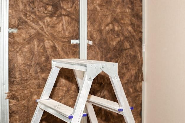 La maison répare une échelle pliante sur fond de mur tapissé de laine minérale pour
