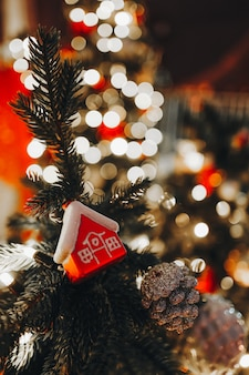 Maison rouge de jouet de noël accrochée à l'arbre de noël avec des lumières festives dorées sur fond