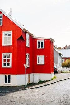 Maison rouge avec toit blanc dans la rue