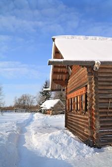 Maison rurale en bois parmi la neige