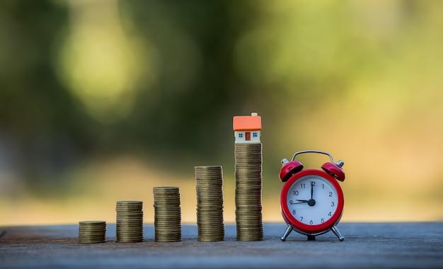 Maison et tirelire, montres, prêts ou épargne pour acheter une maison et un investissement immobilier et commercial dans le futur.