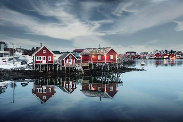 Maison traditionnelle en bois rouge au bord de l'eau dans un village de pêcheurs en hiver
