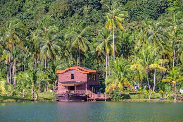 Maison tropicale sous la forme d'un navire dans un grand lagon à côté de la mer dans la jungle avec des palmiers verts. station balnéaire de luxe sur une île en thaïlande. concept de nature et de voyage