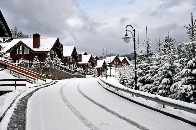 Maison de vacances de chalets en bois dans la station de vacances de montagne recouverte de neige fraîche en hiver.belle rue d'hiver après les chutes de neige.