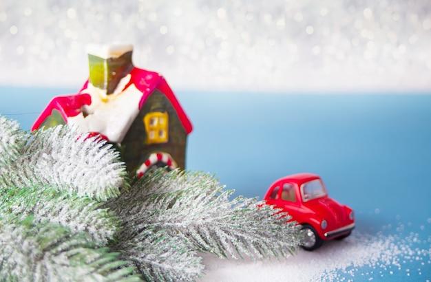 Maison et voiture miniatures. branche d'arbre de noël sur bleu