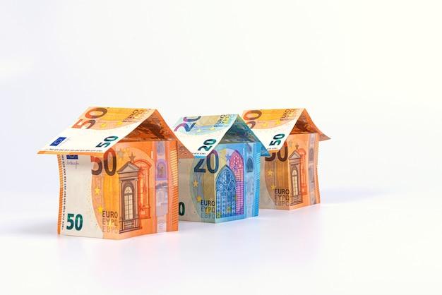 Maisons abstraites de 50 et 20 billets en euros isolés sur une surface légère, concept de prêt immobilier