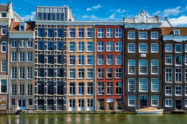 Maisons et bateau sur le canal d'amsterdam damrak avec réflexion. ams