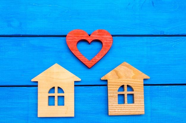 Maisons en bois et coeur sur fond bleu