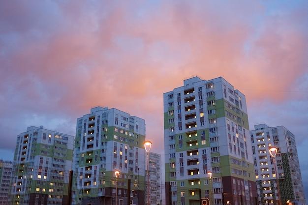 Maisons colorées sur coucher de soleil rose dans un quartier résidentiel.