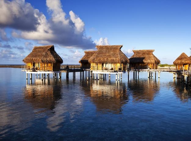Maisons sur l'eau de mer calme et transparente sur un coucher de soleil