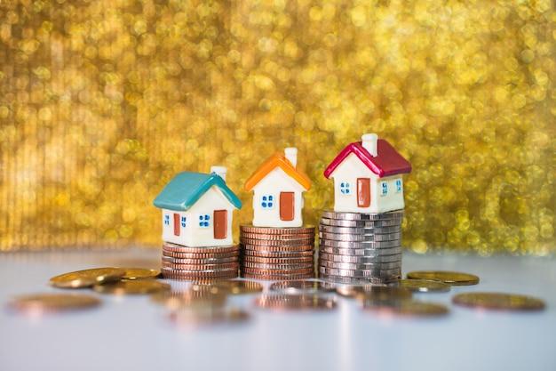 Maisons miniatures debout sur des pièces de pile