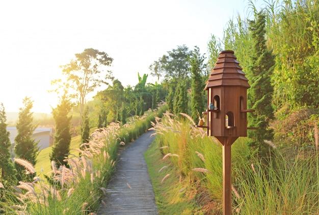 Maisons d'oiseaux en bois près de passerelle dans un champ d'herbe séchée au coucher du soleil.