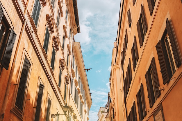 Maisons romaines avec volets, ciel bleu sur la ville, oiseau vole au-dessus d'une ancienne rue de rome, italie.