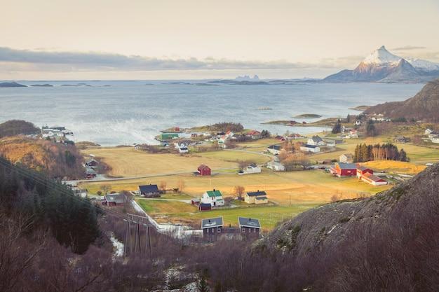 Maisons rustiques colorées typiques de la scandinavie dans la vallée au bord de la mer.