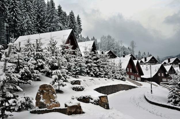 Maisons traditionnelles en bois sur une colline dans les montagnes des carpates entourées de sapins enneigés.