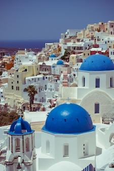 Maisons traditionnelles et célèbres et églises avec des dômes bleus sur la caldera, mer egée
