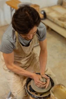 Maître à l'aide de la roue. homme concentré aux cheveux noirs reliant étroitement les mains tout en sculptant un morceau d'argile avec de l'eau