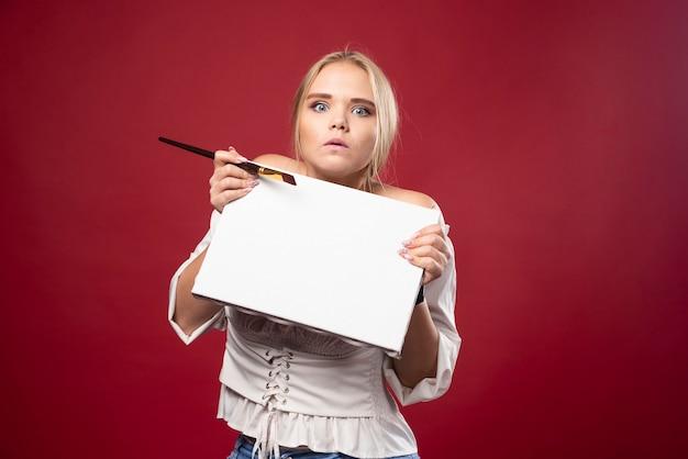 Maître d'art blonde travaillant sur toile avec un pinceau et semble confus.