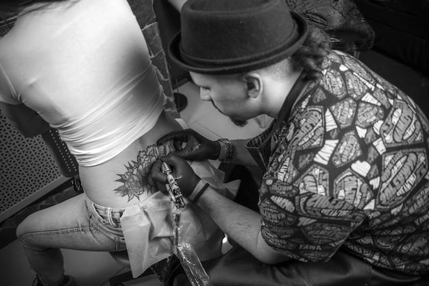 Maître de l'art du tatouage montre un studio de tatouage de coloration de tatouage.