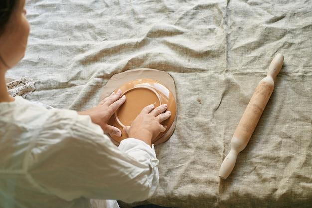 Le maître artisan roule l'argile sur la table, transfère le motif de la serviette sur la masse d'argile