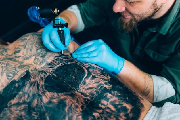 Maître artiste de tatouage fait un tatouage. fermer