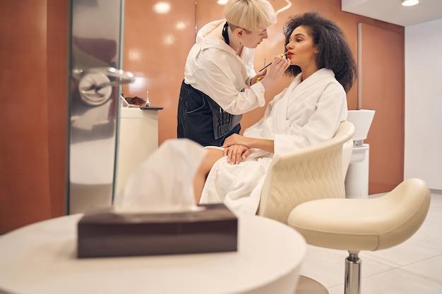 Maître de beauté concentré à l'aide d'un pinceau et appliquant du rouge à lèvres rouge tandis que la belle cliente est assise paisiblement dans un fauteuil