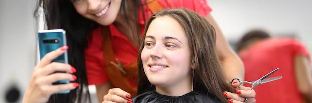 Maître coiffeur avec client regarde l'écran du smartphone dans un salon de beauté.