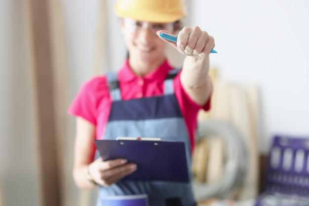 Le maître constructeur souriant tient un stylo et un presse-papiers