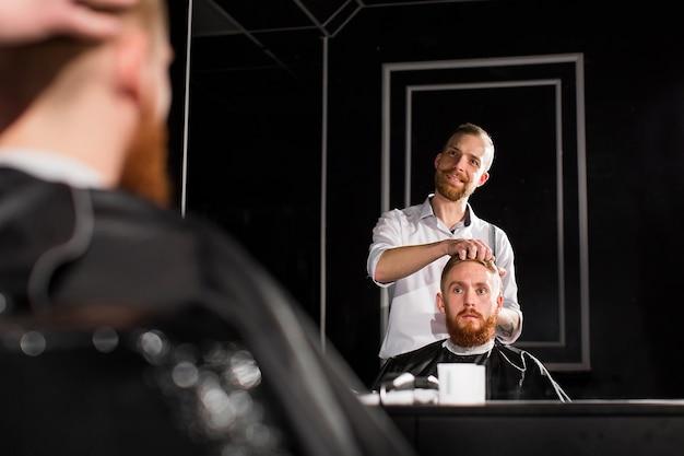 Le maître coupe les cheveux et la barbe dans le salon de coiffure. le coiffeur fait la coiffure à l'aide de ciseaux et d'un peigne en métal.