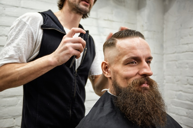 Le maître coupe les cheveux et la barbe des hommes dans le salon de coiffure, le coiffeur fait la coiffure pour un jeune homme