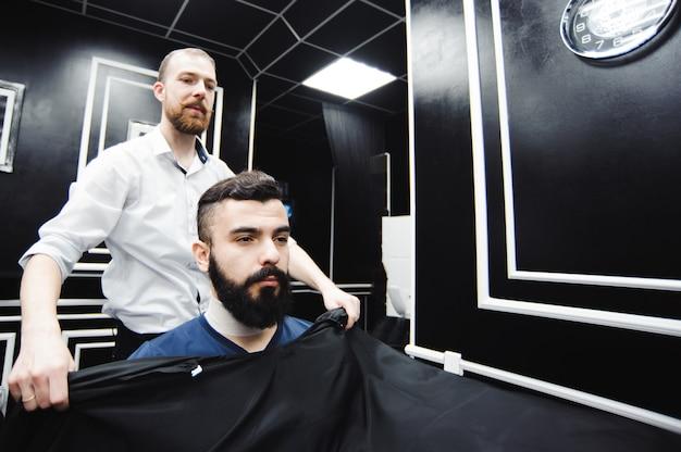 Maître coupe les cheveux et la barbe des hommes dans le salon de coiffure, coiffeur