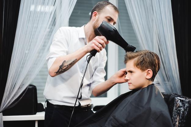 Maître coupe les cheveux d'un garçon dans le salon de coiffure