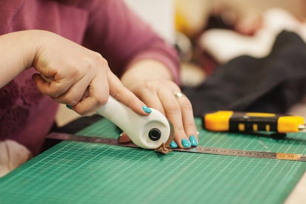 Le maître-couture coupe un morceau de tissu pour un travail ultérieur.