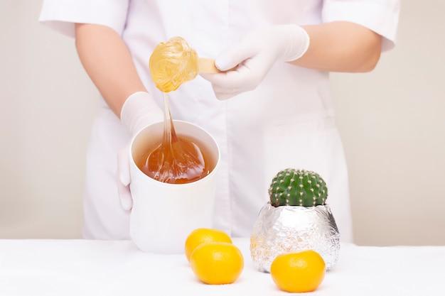 Le maître du sucre tient dans ses mains un pot de pâte à sucre. a proximité se trouve un cactus et des mandarines. concept de peau propre. fond clair.