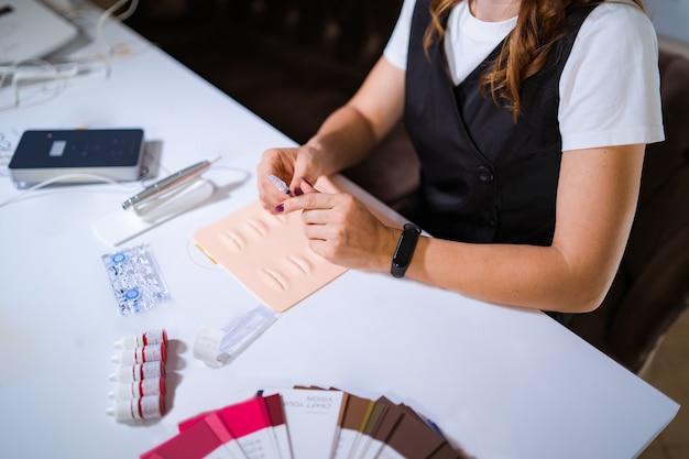 Maître du tatouage permanent avec outil pour microblading, formation au maquillage permanent sur fausses lèvres.