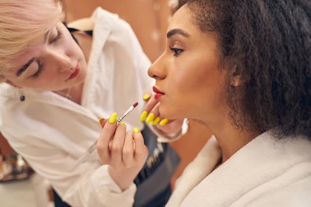 Maître du visage professionnel mettant du rouge à lèvres rouge à l'aide d'un pinceau à lèvres tandis qu'une adorable cliente se sentait calme
