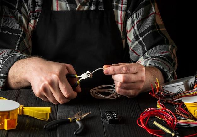 Maître électricien coupe le fil avec une pince diagonale. environnement de travail sur la table d'atelier