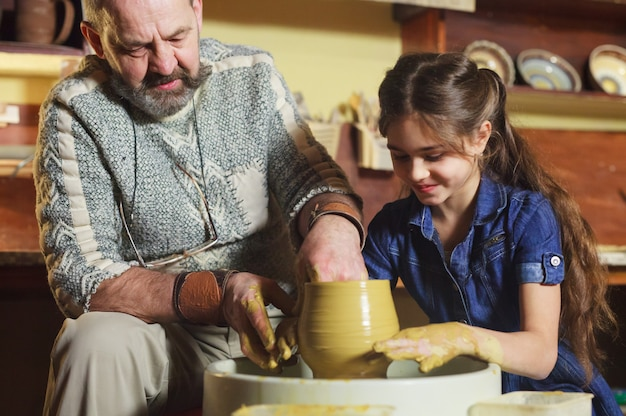 Le maître avec l'enfant moule une cruche en argile.