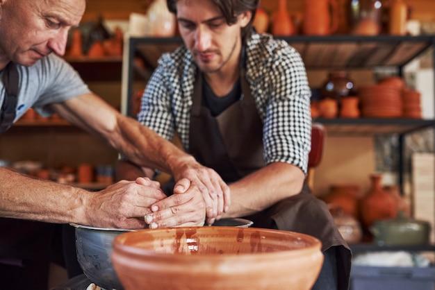 Le maître enseigne l'étudiant. deux céramistes utilisent un tour de potier pour créer un produit en argile fait à la main.