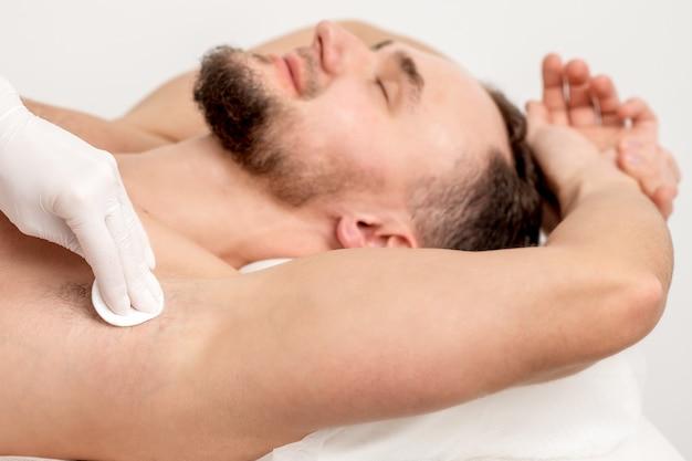 Maître d'épilation essuyant l'aisselle masculine