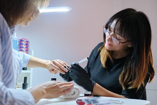 Maître esthéticienne peignant la conception d'art sur les ongles.